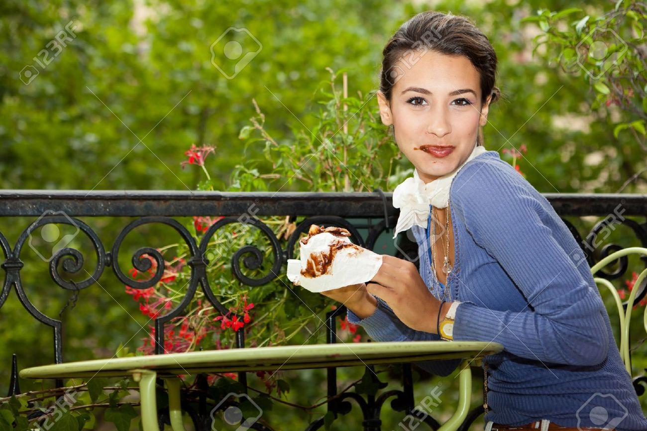 13121917-belle-jeune-femme-appr-ciant-un-pain-au-chocolat-sur-un-balcon-de-paris-banque-dimages